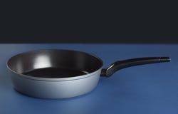 有把柄的煎锅在蓝色背景 免版税图库摄影