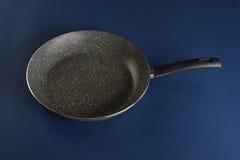 有把柄的煎锅在蓝色背景 免版税库存照片