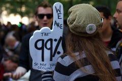 有抗议标志的少妇在Occupy华尔街 免版税库存图片