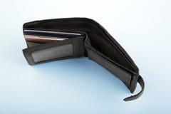 有折扣卡片的一个被打开的皮革黑钱包,在浅兰的背景 没有金钱的钱包 免版税库存照片