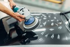 有抛光机的工作者清洗汽车敞篷 免版税库存照片