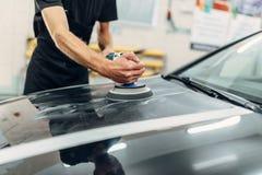 有抛光机的男性收养清洗汽车敞篷 免版税库存照片