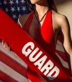 有抢救管和口哨设备的美国妇女救生员反对美国旗子 图库摄影