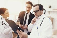 有护士和混乱的商人的老练的医生看身体检查的结果 图库摄影
