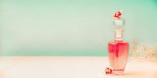 有护肤品的桃红色化妆与花架的瓶或香水在绿松石背景,正面图, banne的桌上 免版税库存图片