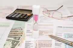 有报税表1040,计算器、笔和美元的滴漏 图库摄影