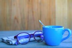 有报纸和眼睛玻璃的蓝色咖啡杯 库存图片