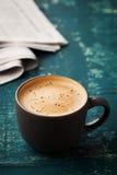 有报纸的咖啡杯在小野鸭土气桌,舒适早餐上 免版税库存照片