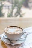 有报纸的热的拿铁艺术咖啡杯在木桌,葡萄酒上 库存图片