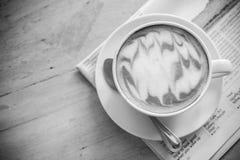 有报纸的热的拿铁艺术咖啡杯在木桌,葡萄酒上 免版税库存照片