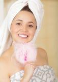 有报道她的头的白色毛巾的美丽的微笑的少妇投入了一块桃红色浴海绵在她的面颊下 免版税图库摄影