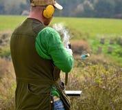 有抽烟的猎枪的枪手在射击以后 库存照片