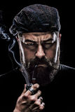 有抽管子的一个厚实的胡子的恼怒的人 免版税库存照片