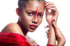有抽象不对称的红色构成的年轻深色皮肤的女孩 图库摄影