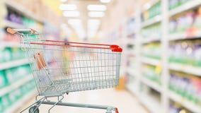 有抽象迷离超级市场的空的红色购物车 免版税库存照片