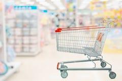 有抽象迷离超级市场走道内部的购物车 库存照片