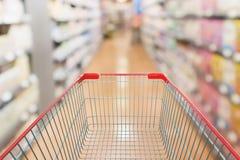 有抽象迷离超级市场走道的空的红色购物车 免版税库存图片