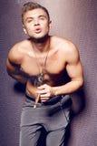 有抽雪茄的赤裸躯干的英俊的性感的年轻人 免版税库存图片