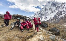 有担子的搬运工在横渡Cho La以后在喜马拉雅山通过 免版税图库摄影