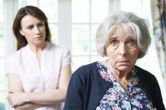 有担心的成人女儿的严肃的资深妇女在家 图库摄影