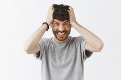 有拉头发的胡子的小便的和困厄的恼怒的欧洲人从握紧牙和皱眉从反感的头里面 库存照片