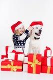 有拉布拉多狗的孩子戴圣诞节帽子 免版税库存照片