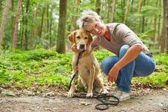 有拉布拉多猎犬的妇女在森林里 库存照片