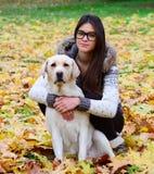 有拉布拉多猎犬的美丽的女孩在秋天森林里 库存图片