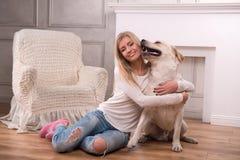 有拉布拉多猎犬的美丽的白肤金发的女孩 库存照片