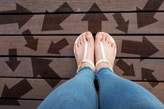 有拉长的方向箭头选择的妇女鞋子 站立在木地板背景的妇女脚和凉鞋 免版税图库摄影