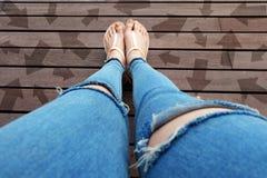 有拉长的方向箭头选择的妇女鞋子 站立在木地板背景的妇女脚和凉鞋 库存照片