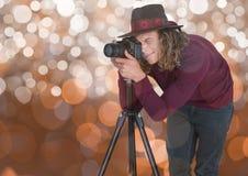 有拍与三脚架的帽子的年轻行家摄影师一张照片 布朗bokeh 免版税库存图片