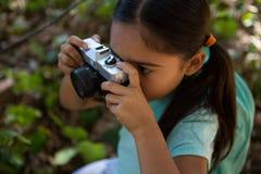 有拍与照相机的背包的小女孩照片在一个晴天在森林里 库存图片