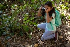 有拍与照相机的背包的小女孩照片在一个晴天 免版税库存图片