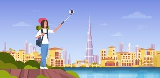 有拍在美好的迪拜市背景的背包的妇女游人Selfie照片 皇族释放例证