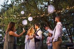 有拍新娘和新郎的照片智能手机的客人在结婚宴会外面 免版税库存图片