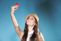 有拍照片她自己的手机的女孩 库存照片