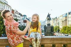 有拍照片的照相机的母亲和儿童游人在布拉格 图库摄影