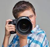有拍照片的照相机的男孩 免版税库存照片