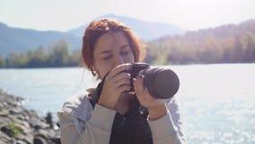 有拍照片的红色头发摄影师的美丽的妇女使用专业照相机户外在远足 女性远足者采取 股票视频
