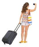 有拍照片的轮子袋子的年轻旅游妇女 免版税库存照片