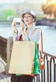 有拍的购物袋的美丽的女孩照片的她自己 库存图片