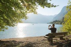 有拍美丽的湖的照片电话照相机的可爱的游人,男性享用的假期旅途在夏天 库存照片