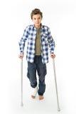 有拐杖和绷带的十几岁的男孩在他的右腿 免版税库存照片