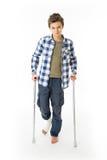 有拐杖和绷带的十几岁的男孩在他的右腿 免版税图库摄影