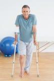 有拐杖的微笑的成熟人在健身房医院 免版税库存照片