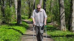 有拐杖的残疾人走在公园的 股票录像