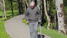 有拐杖的残疾人走在道路的在公园 影视素材