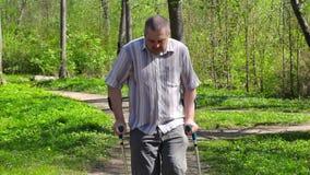 有拐杖的疲乏的残疾人走在公园的 股票录像