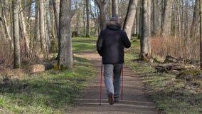有拐杖的远足者在道路在公园 股票录像